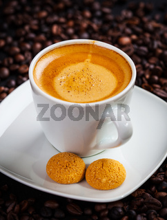 Cup of espresso with coffee beans and biscuit