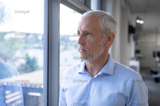 Senior businessman looking through window at modern office