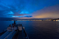 Approaching the illuminated norwegian city Trondheim in early dawn seen from the sea looking over the bow of cruise ship MS Lofoten