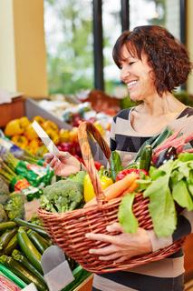 Frau mit Einkaufsliste kauft Gemüse im Supermarkt