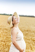 Young pretty pregnant woman outdoors on sunset in the field