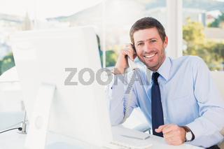 Smiling businessman phoning at his desk