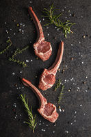 Slices raw lamb chops with salt, pepper and rosemary