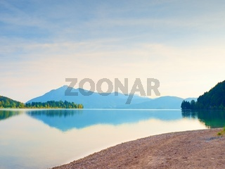 Romantic sunset at mountain lake. Stony beach and dark mountains in water mirror.