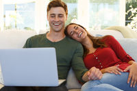 Caucasian couple sitting on a couch using laptop