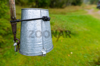 Empty metal bucket tied upside down on stick