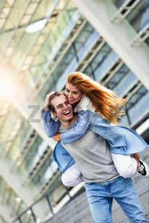 Happy young caucasian couple having fun with piggyback outdoors