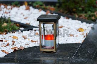 moderne Grablaterne aus Metall mit brennender Kerze auf einem Grab