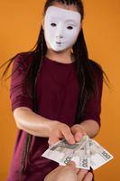 A male hand reaches for paper bills given by an anonymous young woman. An isolated figure on a solid orange color.