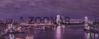 Panorama of the circular highway leading to the illuminated Rainbow Bridge with Cargo and