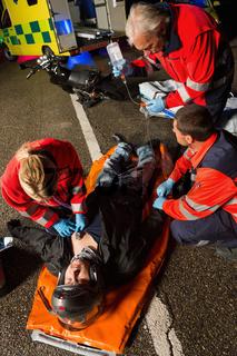 Paramedical team helping injured motorcycle driver