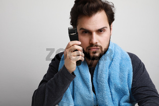 Headshot portrait of handsome young man shaving his beard in bathroom, holding shaver machine. Space for text.