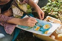 Closeup of woman's hands paiting in oils bright flowers outdoors