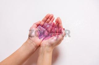 hands holding glitters on white background