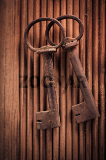 Two vintage keys on wooden background. Top view.