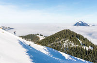 Man with two dogs running down snow mountain with amazing view to mountains above inversion valley fog layer. Sea of clouds. View from Rangiswangerhorn, Alps, Allgau, Bavaria, Germany.
