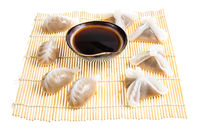 various Dim sum and soy in bowl on mat isolated
