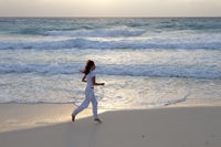 woman jogging on the edge of the sandy beach at sunrise