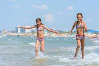 Two girls joyfully run along the seashore on a warm summer day