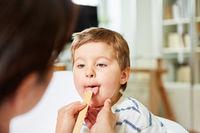 Kind mit Halsschmerzen bei der Untersuchung
