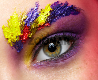 Close-up photo of female eye with unusual art make-up and face painting on brows and around eye