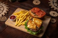 Disassembled beef burger with fried cheese, slices tomatoes served with french fries on a decorative wooden board with tomato sauce with wooden decorative pieces of simple mechanism