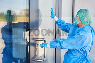 Mitarbeiter vor Klinik gibt Handzeichen an der Tür vor Eintritt