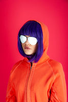Alternative funky girl with blue hair on a bright pink background. Close up fashion portrait young beautiful woman in hoodie and white glasses. Unusual youth fashion concept. Hot image.