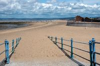 Sandy path to Morecombe beach with blue handrails