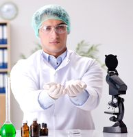 Young doctor working in the lab with microscope