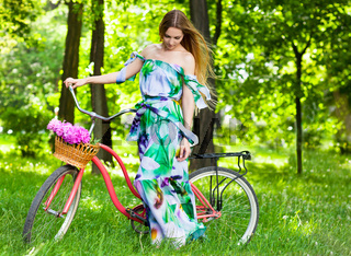Beautiful blond woman wearing a nice dress having fun in park with bicycle carrying a beautiful basket full of peony