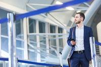 Geschäftsmann mit Smartphone am Flughafen Terminal