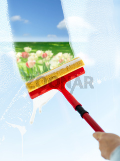close up of hand cleaning window with sponge