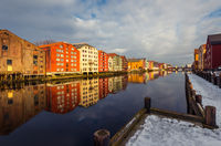 Old historic storehouses along the river Nidelva with colorful painted facades in Trondheim on beautiful winter day