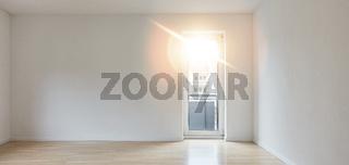 Leerer sonniger Raum als Wohnzimmer mit Balkon