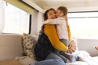 Happy mother and daughter in caravan