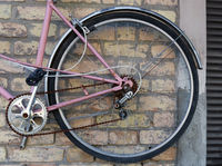 Wheel of  broken pink women's  bike hanging on a yellow brick wall