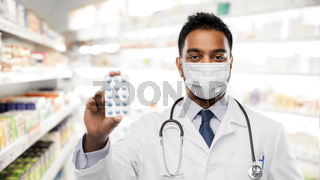 indian male doctor or pharmacist in mask with drug
