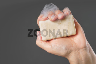 Caucasian male hand holding plain bar of soap with lather and bubbles