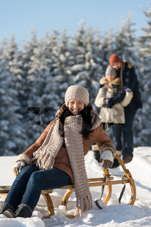 Young woman sitting winter wooden sledge