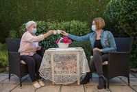 Senior woman and daughter with face masks drinking coffee at safety distance in the garden