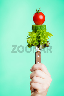 Stack of vegetales on knife in hand