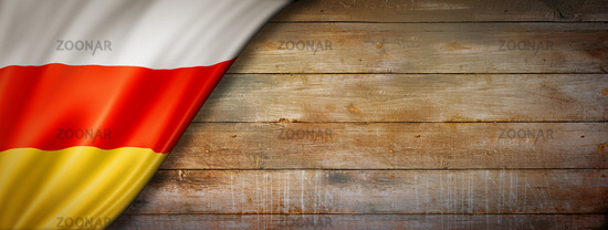 South Ossetia flag on vintage wood wall banner