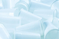 Disposable white plastic cups as background. Environmental concept. Non-compostable waste. In blue t