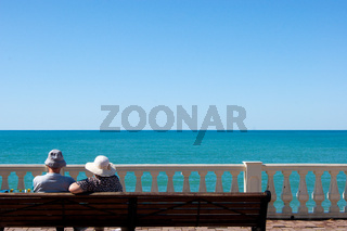 a couple of adults sits on the promenade and looks out at the sea