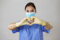 Medical professional forms the symbol for love with her fingers in front of her.