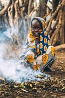 TOPOSA TRIBE, SOUTH SUDAN - MARCH 12, 2020: Child in ornamental cloth smiling and looking at camera while sitting on haunches near small flame emitting smoke in village of Toposa Tribe in South Sudan, Africa