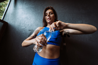 Fit woman posing on the camera. Girl opens a water bottle. Beauty of modern sport.
