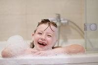 little girl in bath playing with soap foam