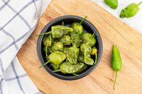 Top view of Cooked Padron peppers in a a bowl on wooden table